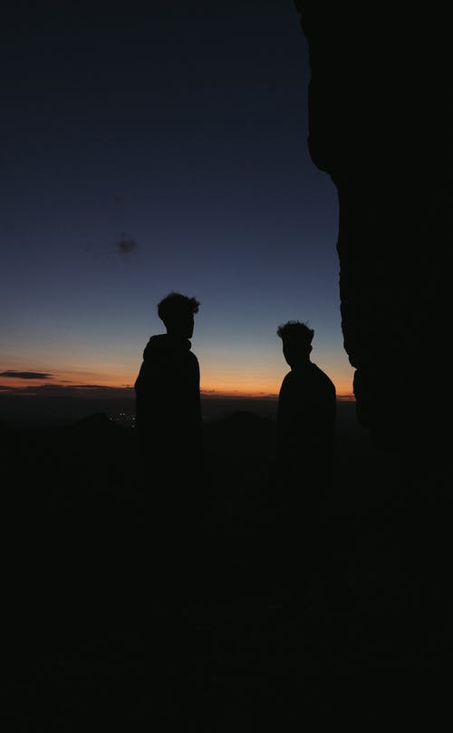 Anonymous guys standing on viewpoint in mountainous valley in evening