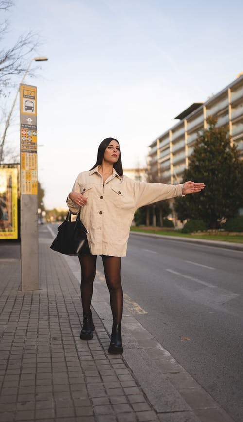 Full body of trendy young female with long dark hair in casual outfit standing on pavement with outstretched arm while catching  taxi in city