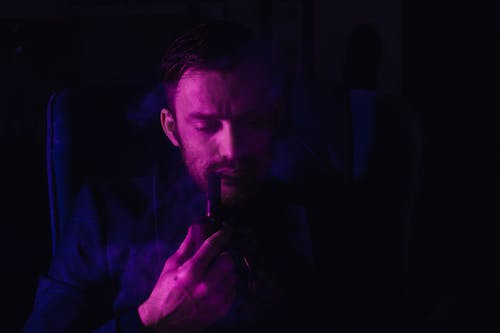 Thoughtful young bearded male in elegant suit smoking pipe while resting in armchair in dark room with purple neon lights