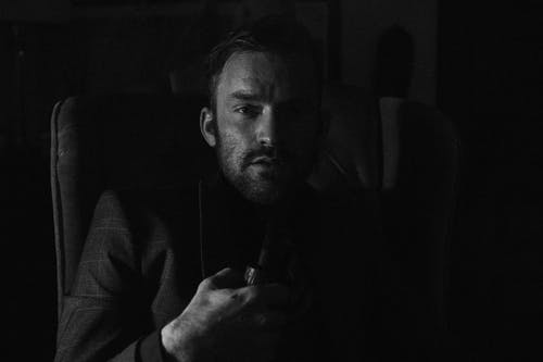 Black and white of serious young male bearded man in stylish elegant suit smoking pipe while resting in comfortable armchair and looking at camera