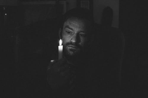 Black and white of adult bearded male looking at glowing flame of wax candle