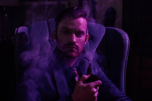 Stylish man with smoking pipe in armchair