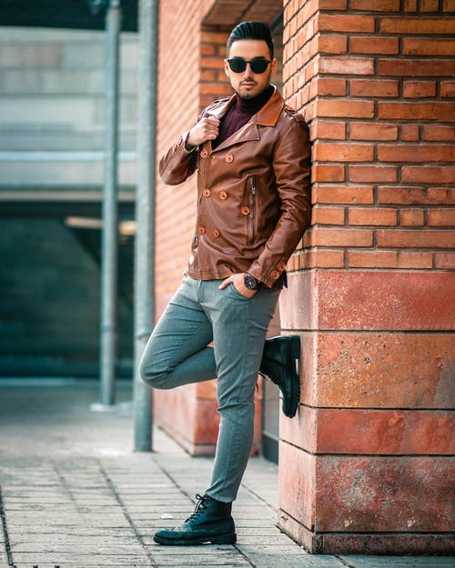 Man Leaning on Brown Brick Wall