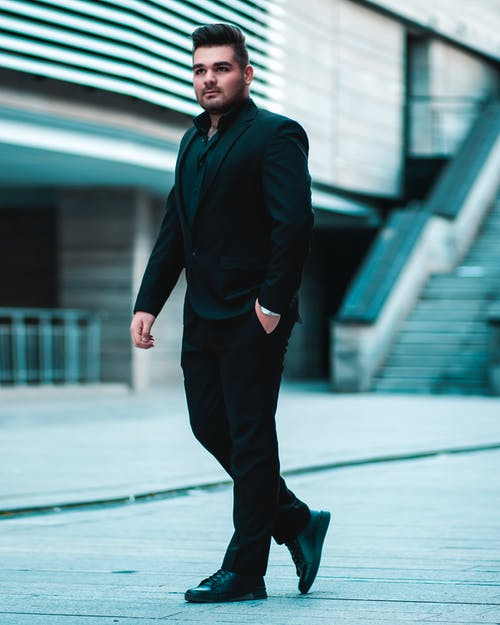 Man in Black Suit Walking with Hand in Pocket