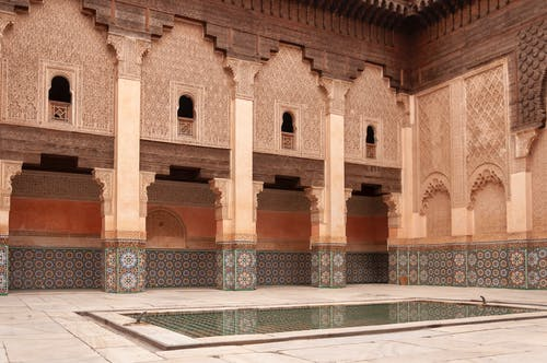 Main courtyard of ancient Ben Youssef Madrasa with arched passage and walls decorated with arabesque ornaments on sunny day in Marrakesh