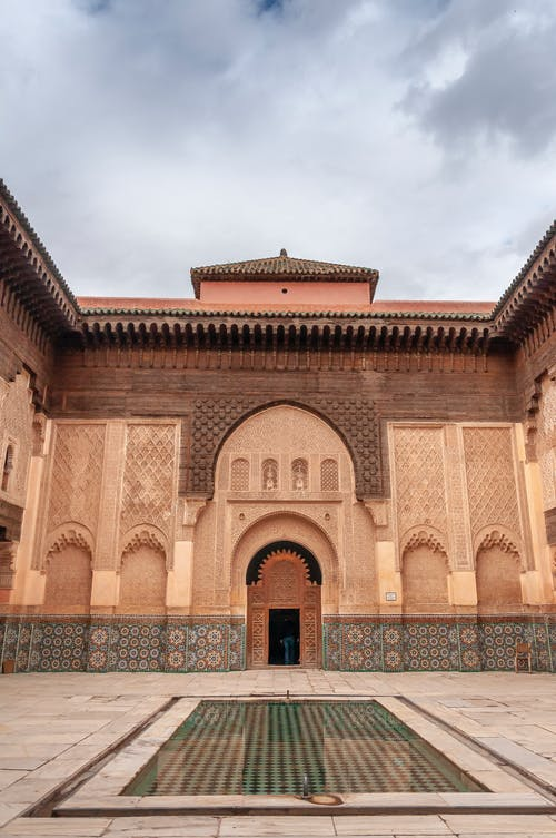 Water basin in courtyard of ancient Ben Youssef Madrasa with ornamental walls decorated with arabesque and zellij tilework against overcast sky in Marrakesh