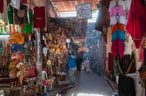 Unrecognizable people walking in local bazaar near stalls with various goods and souvenirs and traditional clothes on sunny day in Marrakesh