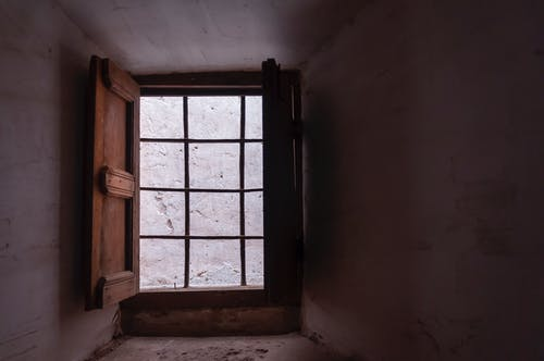 Old wooden window with metal grid in small room with shabby white wall in daytime