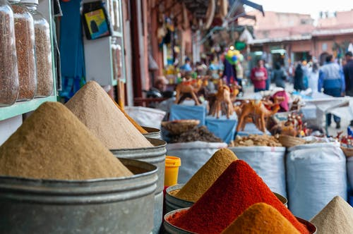 Metal containers with heaps of assorted aromatic colorful spices placed on stall in local outdoor market