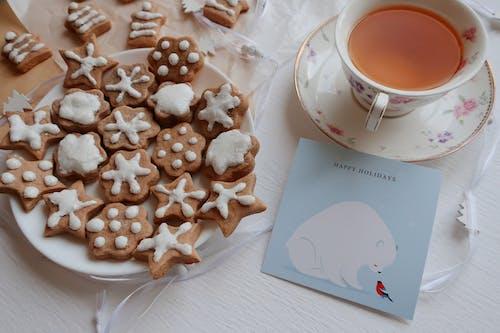 White Ceramic Mug on White Ceramic Saucer Beside White and Brown Heart Shaped Cookies