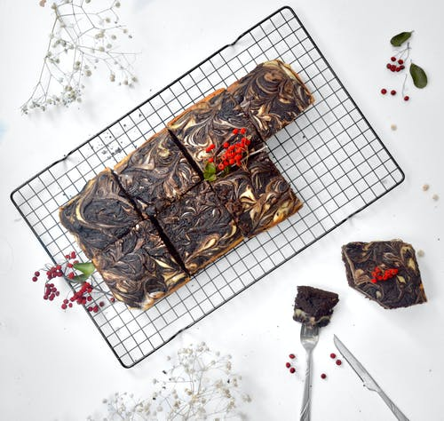 Top view of appetizing chocolate brownie cut into squares and decorated with ripe berries placed on metal grid on table