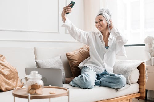 Woman Taking a Selfie on Her Cellphone After Taking a Bath