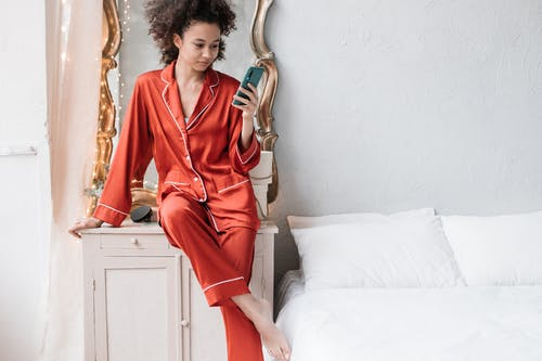 Woman in Red Pajamas Using Her Cellphone Near The Bed