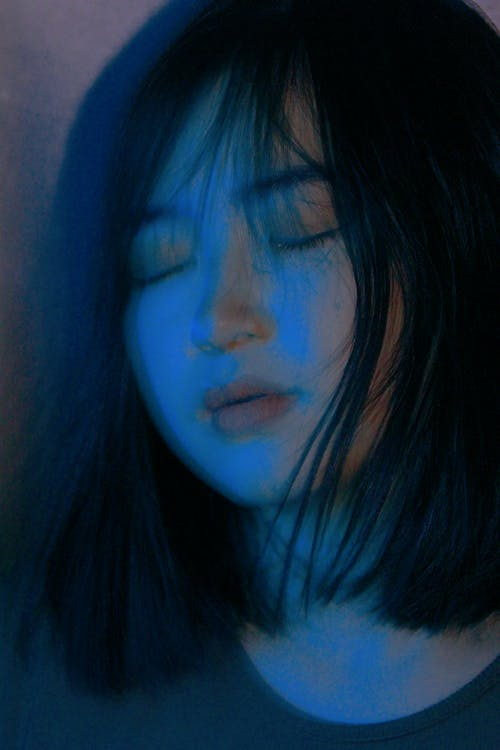 Crop Asian woman with eyes closed in darkness
