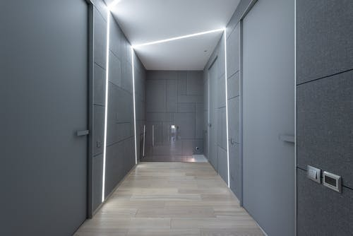 Interior of contemporary hallway of creative space with parquet and gray walls with doors and modern bright illumination on ceiling and walls