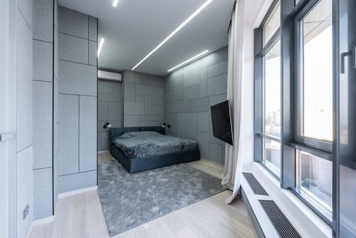 Interior of modern light apartment with bed near carpet with TV near windows and curtains in day