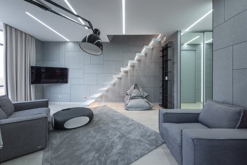 Living room with sofas near table and TV with stairs