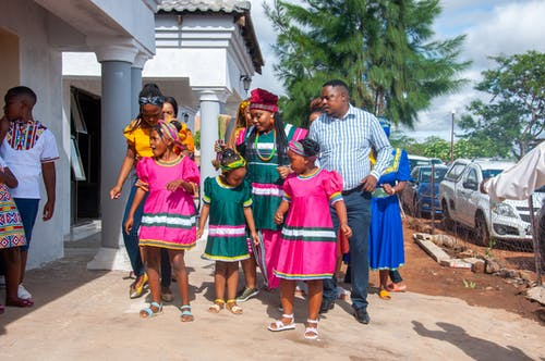 Cheerful African family in bright pink and green national dresses and elegant suit near house