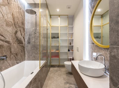 Modern light bathroom interior with white sink and faucet on counter near mirror and toilet near bath