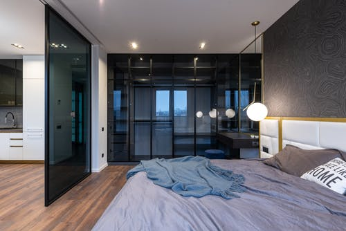 Interior of light spacious studio with soft bed with pillows near lamp and glass doors near kitchen