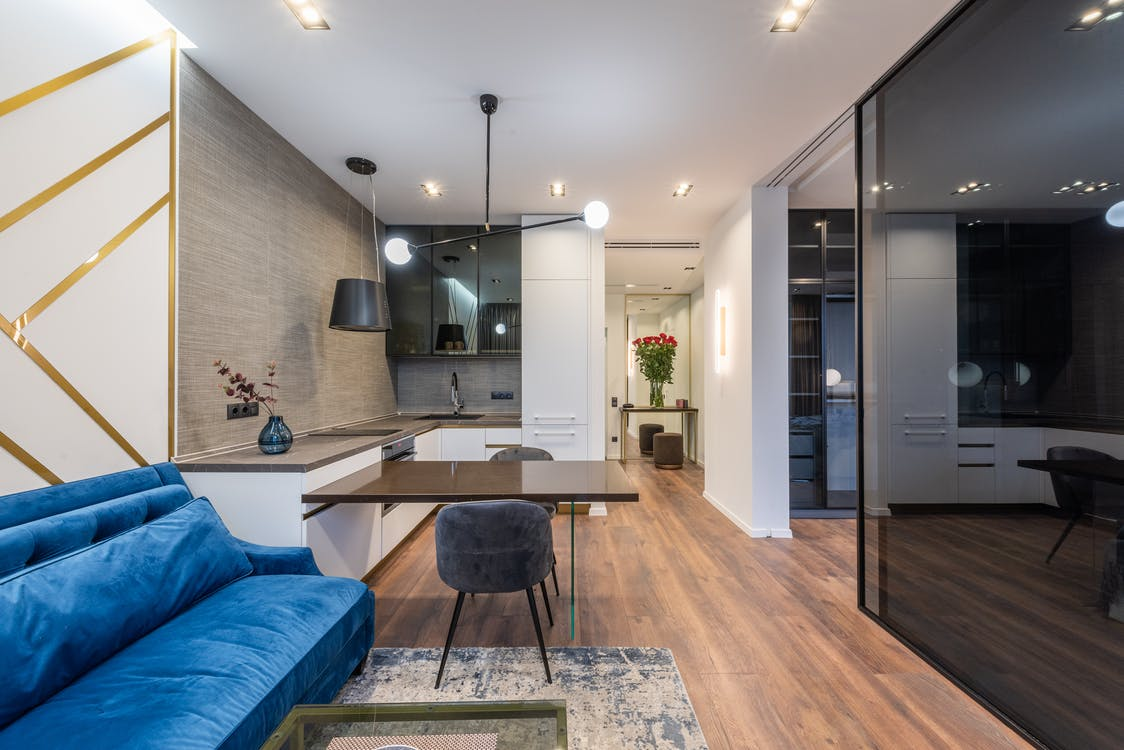 Interior of modern apartment with blue sofa near table with chairs near kitchen with counter near glass door