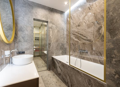 Modern bathroom with sink and faucet on counter near bath