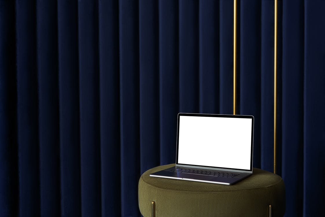 Laptop placed on pouf near curtain
