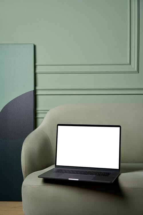 Laptop with white screen placed on soft sofa with big painting on floor near green uneven wall in bright apartment