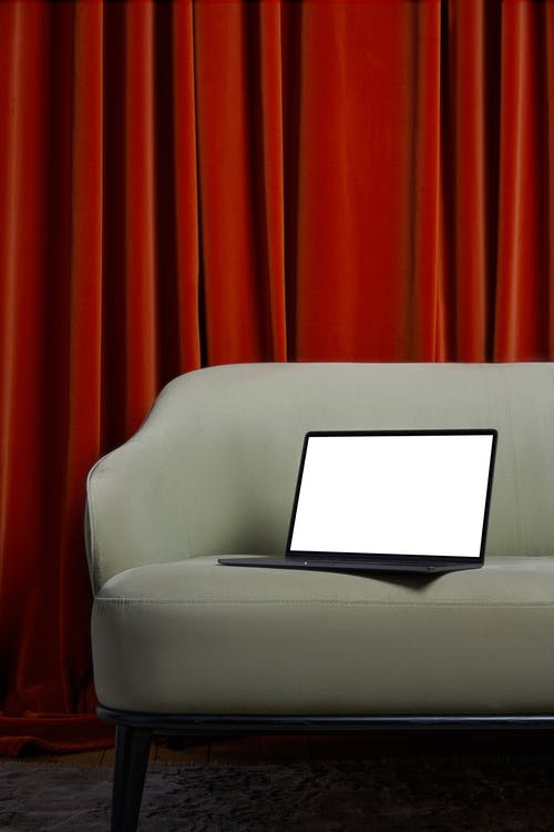 Laptop with white screen placed on soft couch on carpet near red curtains in bright room