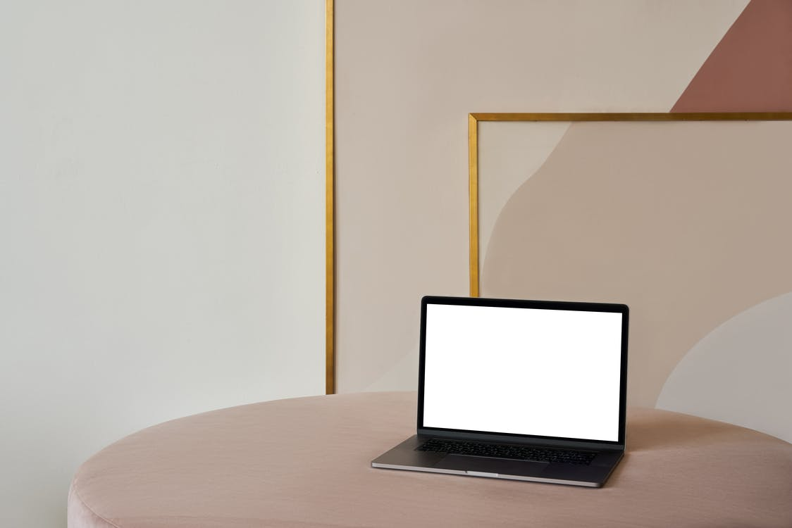 Laptop with white screen placed on soft beige pouf near framed paintings and white wall in light room