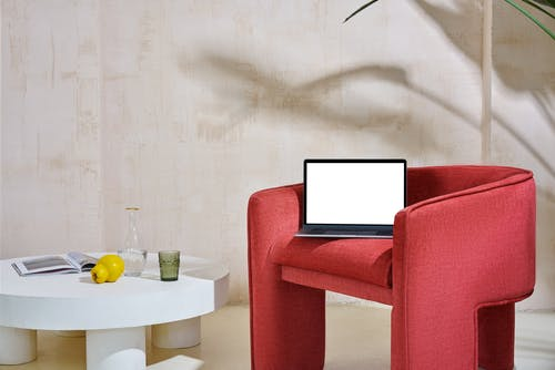 Laptop on armchair near table with glassware in apartment