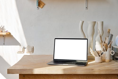 Netbook with white screen placed on wooden table near uneven curved ceramic vase near holders with brushes and tools near shelf in light workshop with white wall