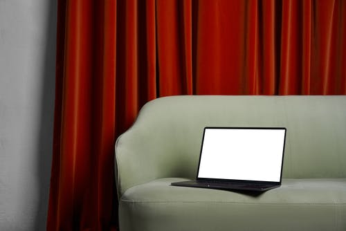 Laptop on couch near red curtains and wall