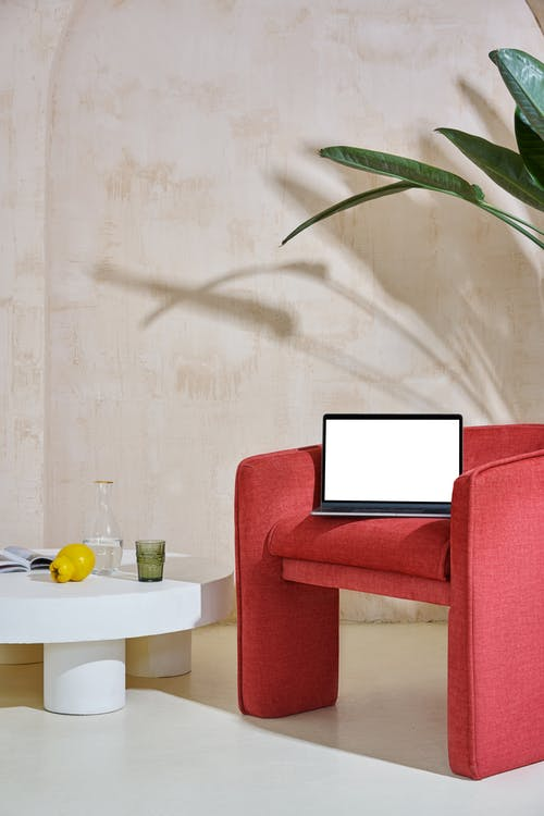 Laptop with white screen on red armchair near small white table with glass near jug with water and apple with magazine and plant with green leaves near wall in room