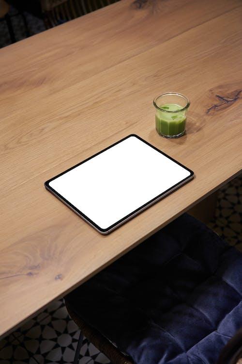 棕色木製的桌子上的白色平板電腦