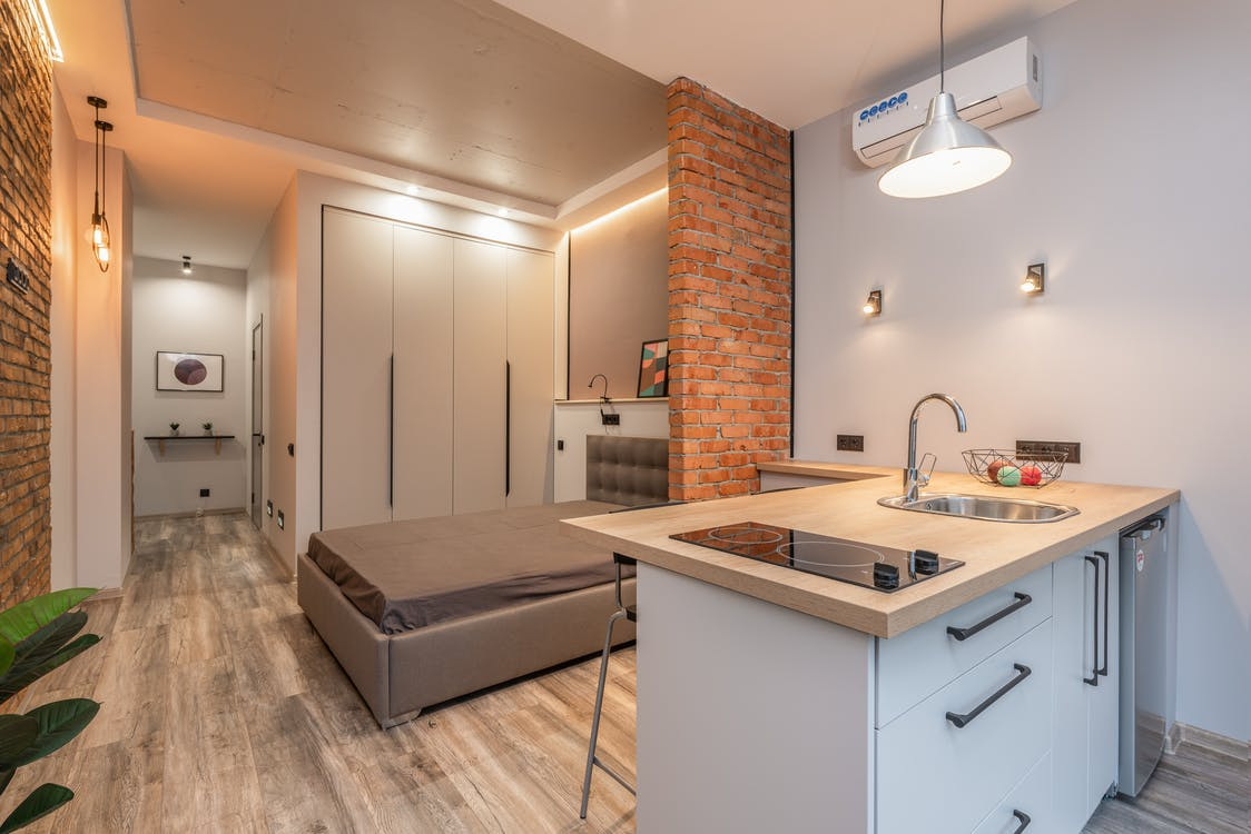 Miniature kitchen with modern appliances and bedroom behind brick partition in small loft style apartment