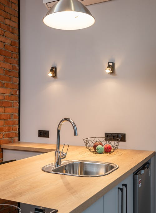 Interior of contemporary apartment with kitchen counter with built in sink and pendant lamp