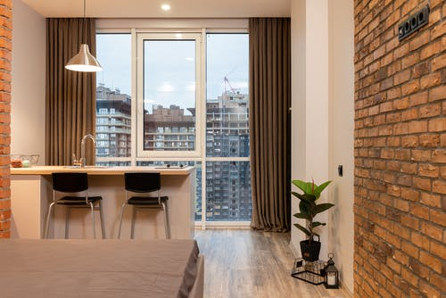 Contemporary apartment interior with bed and kitchen counter and overlooking floor to ceiling window