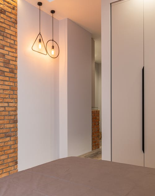 Fragment of modern home design in loft style with minimalist finish of walls and floor and geometric lamps with opened light bulbs and built in wardrobe