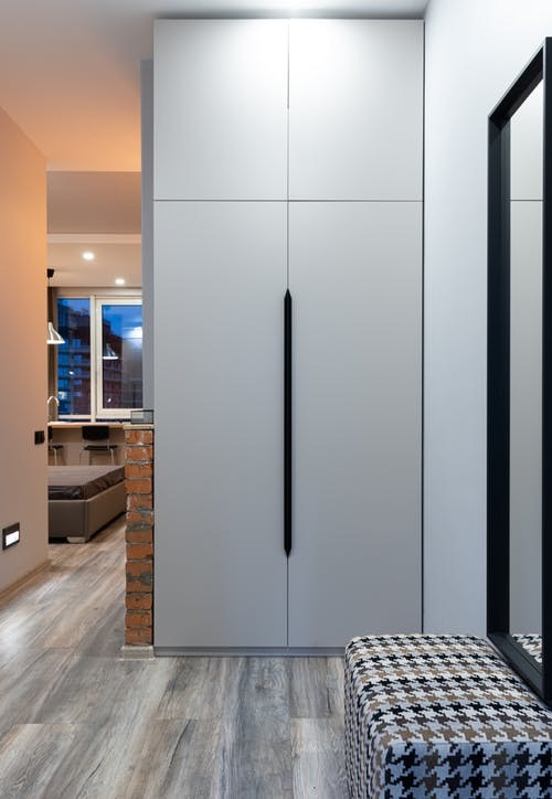 Interior of modern flat with cabinet near pouf and mirror