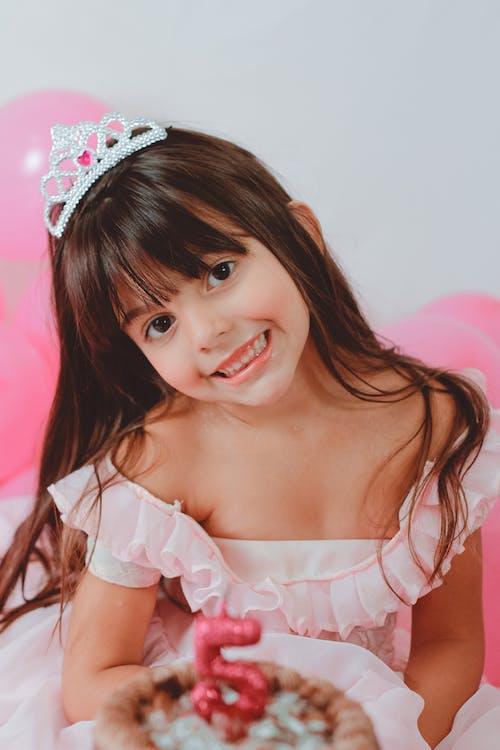 Cute girl in shiny diadem with birthday cake