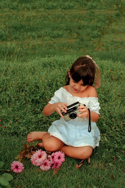 Cute little girl with vintage photo camera on green lawn