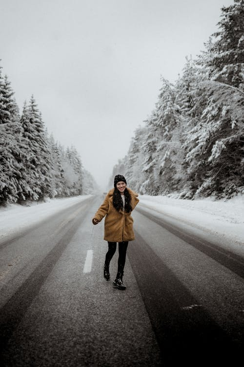 Full body of happy female in warm outerwear running on asphalt roadway between evergreen trees