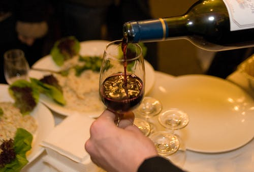 Close-Up Shot of a Person Pouring Red Wine on a Glass