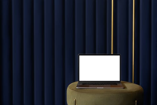Contemporary netbook with empty screen for convenient freelance work against blue striped wall