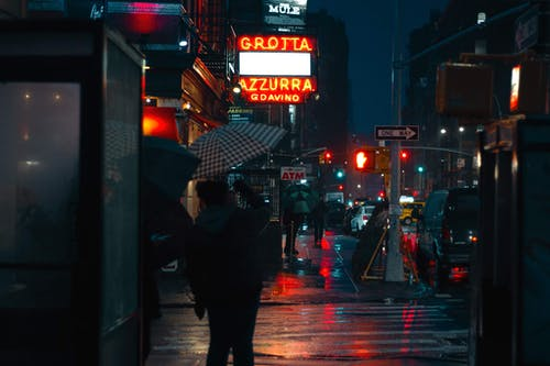 Busy urban city street crowded with pedestrians and illuminated by electric lights in rainy autumn evening