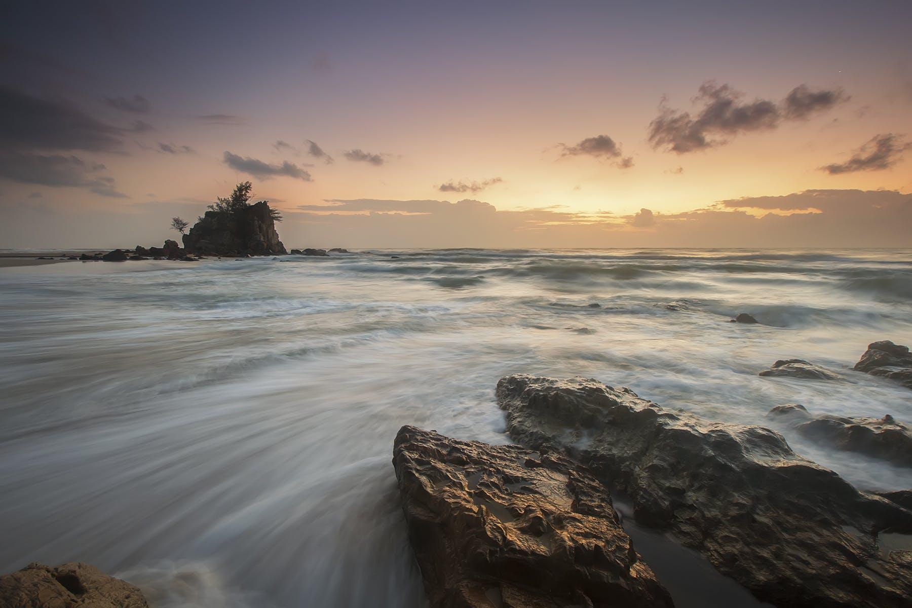 Rocks Near Body of Water Under Orange Sky during Daytime