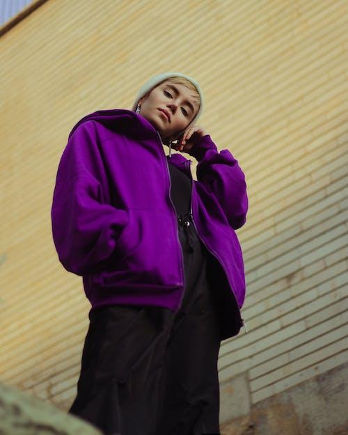 Trendy woman standing near wall in street