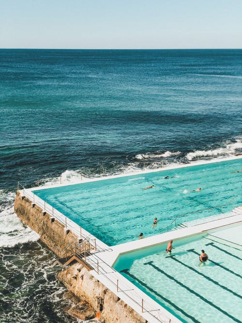 Aerial View of People Swimming in the Pool near the Ocean