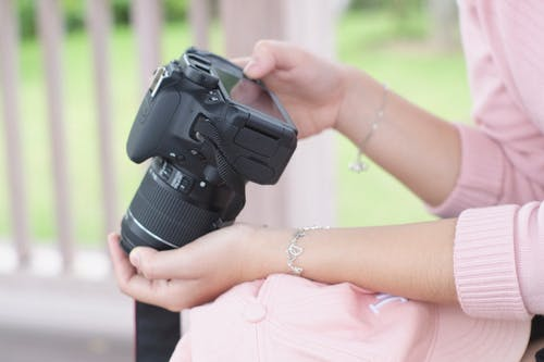Close-Up Shot of a Person Holding a Black DSLR Camera